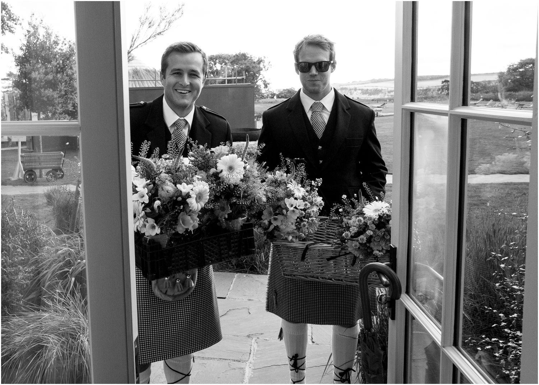 ushers holding wedding flowers wearing northumberland tartan