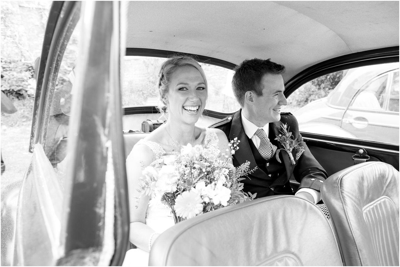 bride and groom in vintage morris minor at studland wedding