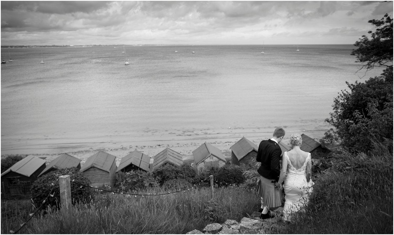 bride and groom walk by beach huts for Harry Warren House Dorset Studland Wedding Photographer