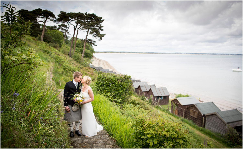 bride and groom kiss by beach huts for Harry Warren House Dorset Studland Wedding Photographer