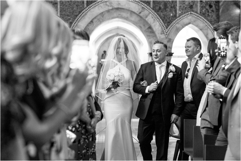 bride walks down the aisle at fitzrovia chapel wedding