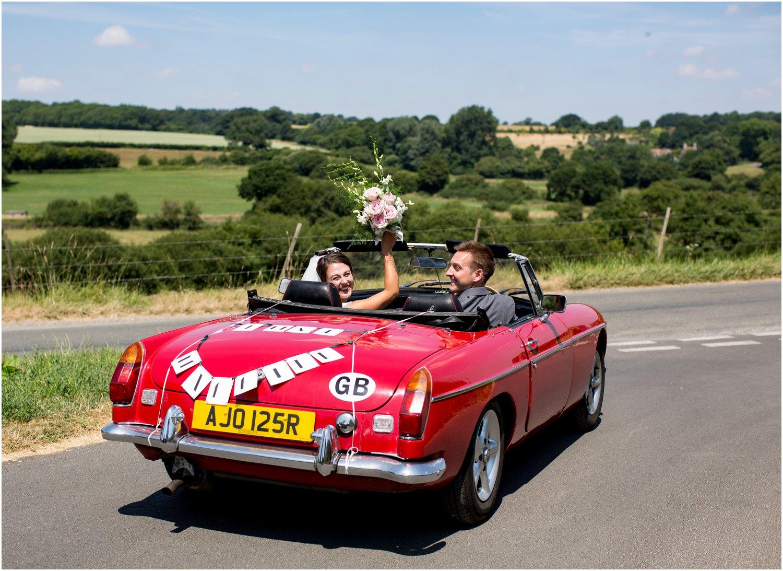 just married couple leaving wardour castle in mg midget car
