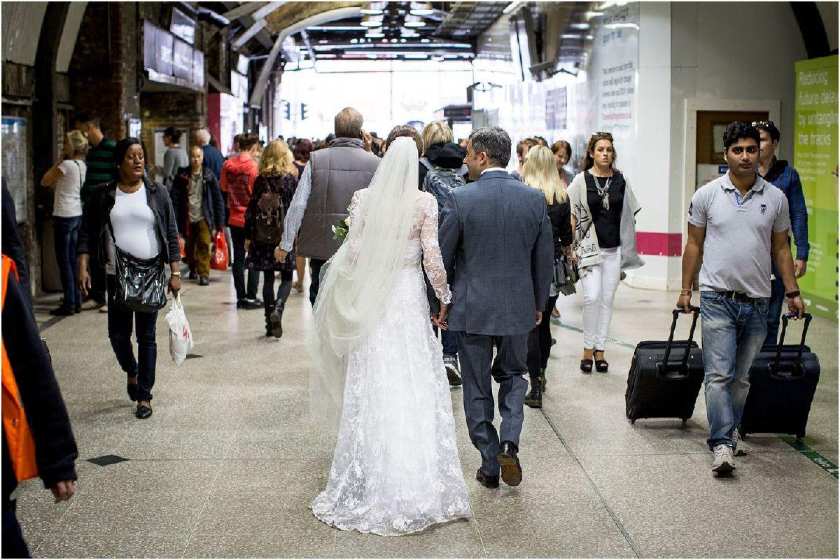 bride and groom walking through Tower Bridge Station